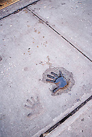 Wet handprint in concrete on sidwalk