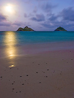 A full moon graces the Mokolua Islands and Lanikai beach with light.