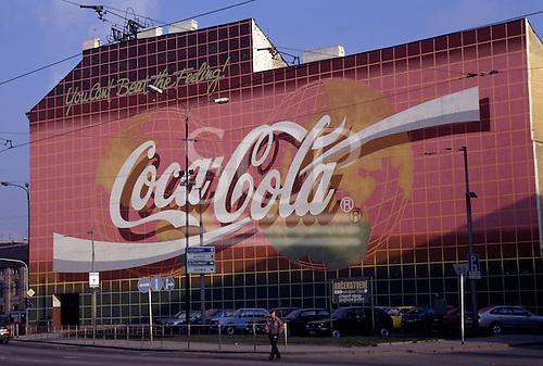 "Prague, Czech Republic. Massive ""Coca - Cola"" advertisement on a wall; signs in Czech under; cars parked."
