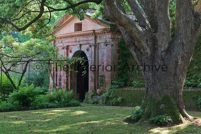 A brick grotto with a neo-classical pediment and antique masks is flanked by ancient moss-covered walls and lush ferns