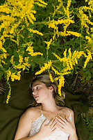 Blonde woman laying on grass surrounded by goldenrod<br />