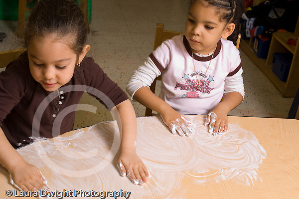 Education preschoool children ages 3-5 sensory activity two girls rubbing shaving cream on table top  one girl watching another horizontal