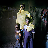 20 year old Amina, a young pregnant mother with her children Aichadou, 6, and Ibrahim, 4. They fled her home village in Nigeria and are now living in the only permanent structure, a small derelict concrete out-building, in this IDP camp. They now survive on just one meal a day.<br /> <br /> <br /> 'In the night they came. They took the village and said 'who wants to come with us?' and those that didn't want to come with them, they killed. They did this a few times and this was the reason why I left and came here. I ran from Nigeria to a village called Double. This village was then also attacked and I ran for three days with everyone to here. I have not seen my husband since the attacks. I've had no news from him since. I hope that my husband ran away during that attacks and that he's in Chad.<br /> <br /> 'I go into the forest and cut wood and sell it in the market. I use the money to buy something to eat. If I don't have any firewood I don't eat any food for the day. I am worried about my pregnancy and what might happen. <br /> <br /> 'When I can buy food, I buy rice, maize and millet. How many times I eat a day depends on the money and resources I have. We use what we find in the bush to eat once or twice a day. If we don't have anything then we don't eat. If I don't have money, I go to the other people here and ask them if they can help, at least food for my children. I may not eat, but not my children, they have to eat at least once a day. And if we don't have anything, I go to the forest and take some leaves and eat those. I am very very worried, all day all I can think about is my children, how do I feed them? It's very difficult for me. <br /> <br /> 'I thank God that I have my children and that I arrived here safely. I hope I will have the chance to be happy in the future. I hope I will be reunited with my husband. I need to see my husband again, it's difficult now, but I hope one day to see him again.<br /> <br /> 'I really like it here because it's a peaceful place. I want to remain here because it's very safe.'
