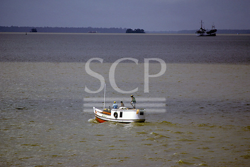 Belem, Para State, Brazil. Small riverboat and ocean going ship on the Amazon River with the far bank visible.