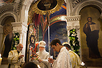 Switzerland. Geneva. Easter at the Russian Church. The church is a lovely 19th-century Russian Orthodox church and designed in a Byzantine Moscovite style. The church's full name is Cathédrale de l'Exaltation de la Sainte Croix. The Archbishop Michael with his mitre during the religious service on the night of Easter Sunday. He holds in both hands the Paschal Trikirion which is a liturgical triple-candlestick used at Easter time in the Eastern Orthodox ceremony. It is used from the commencement of the celebration of the Resurrection during the Paschal Vigil. The nighttime liturgy is a blessing of Easter fire with candles and the celebration of the Easter Proclamation of the Resurrection of Jesus Christ. A large religious painting on the nave's wall represents God the Father. In mainstream trinitarian Christianity, God the Father is regarded as the first person of the Trinity, followed by the second person God the Son (Jesus Christ) and the third person God the Holy Spirit. Other paintings of Jesus Christ and the Virgin Mary. Archbishop Michael (Secular name - Simeon Vasilyevich Donskoff; born on 29 March 1943) is a bishop of the Russian Orthodox Church Outside of Russia, Archbishop of Geneva and Western Europe. Easter, also called Pascha or Resurrection Sunday is a festival and holiday celebrating the resurrection of Jesus from the dead, described in the New Testament as having occurred on the third day of his burial after his crucifixion.The Russian church serves not only the Russian community but also Bulgarians, Serbs, Coptic Christians and other Orthodox worshippers who do not have their own church in Geneva. 16.04.17 © 2017 Didier Ruef