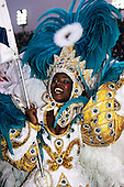 Rio de Janeiro, Brazil. Smiling girl flag bearer in white, turquoise and gold carnival costume.
