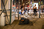 NEW YORK, NY — SEPTEMBER 24, 2020:  A person resting in the warm air rising from a subway grate watches as demonstrators protest against a Kentucky Grand Jury decision to not directly indict the officers involved in the shooting of Breonna Taylor, a 26 year-old EMT who was killed in her Louisville home by police on March 13th of this year, on September 24, 2020 in New York City.  Former police detective Brett Hankison faces three felony charges of wanton endangerment.  Photograph by Michael Nagle