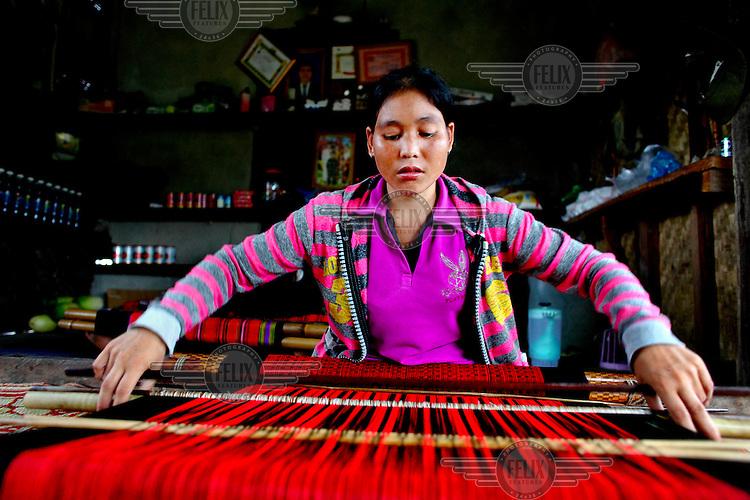 Khornsai (26) weaving on a hand loom.