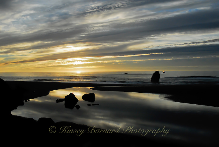 Sunset at Gold Beach Oregon as fishing trawler heads home.