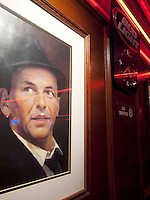 USA. New York City. A framed drawing of Frank Sinatra (1915-1998. American singer and actor), a Bud Light sign and a no smoking forbidden sign on the wall in a cafe in Midtown Manhattan. 24.10.2011 © 2011 Didier Ruef