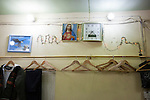 21/10/14. Erbil, Iraq. Coat-hangers and a picture of Jesus Christ are seen on the wall of Wassam and Milad's uncle Amir's tailoring shop in Ainkawa.