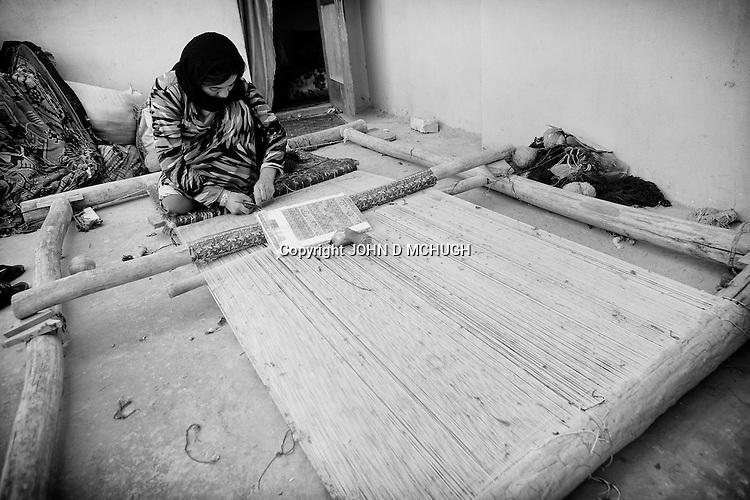A woman weaves a carpet on a loom in her home in Mazar-e Sharif 28 September 2013. (John D McHugh)