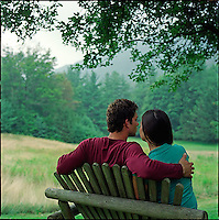 Couple, sitting on bench with backs to camera<br />