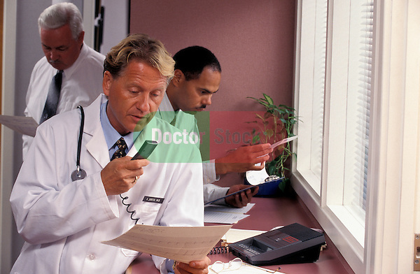 doctor dictating notes about consultation into microphone in office