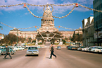 Vintage view of two business men crossing the street in front of the Texas State Capitol and Christmas lone star decorations strung along Congress Avenue from December 1960 - Stock Image.