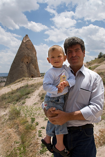 This father and son live in the tufa shown in the background -- one of the thousands of cave dwellings in Cappadocia. With the outer layers of rock now washed away by erosion, one can see the honeycombed structure of tunnels and rooms that likely held many families. The easily carvable rock, called tufa, was home to over 3000 cave houses, churches and monasteries.
