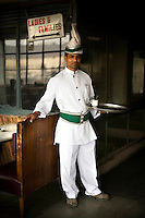 A waiter with a turbaned headress and cumberbund in the Indian coffee house, Baba Kharak Singh Marg. The coffee house dates back almost fifty years, first in central Connaught Place, then Janpath and now at the top of a rather shabby shopping centre. Where it is still run by the Indian Coffee Workers Cooperative Society. Once a regular haunt for politicos in Delhi, its clientele is still renowned for being well-read and intellectual.