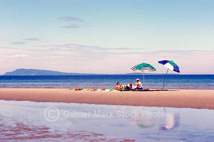 """People sunbathing on the Beach at Qualicum Beach, in the """"Oceanside Region"""" of Vancouver Island, British Columbia, Canada"""