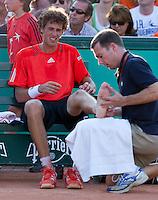 24-05-10, Tennis, France, Paris, Roland Garros, First round match, Robin Haase  krijgt een behandeling aan zijn been in de 5e set van zijn partij tegen  Almagro