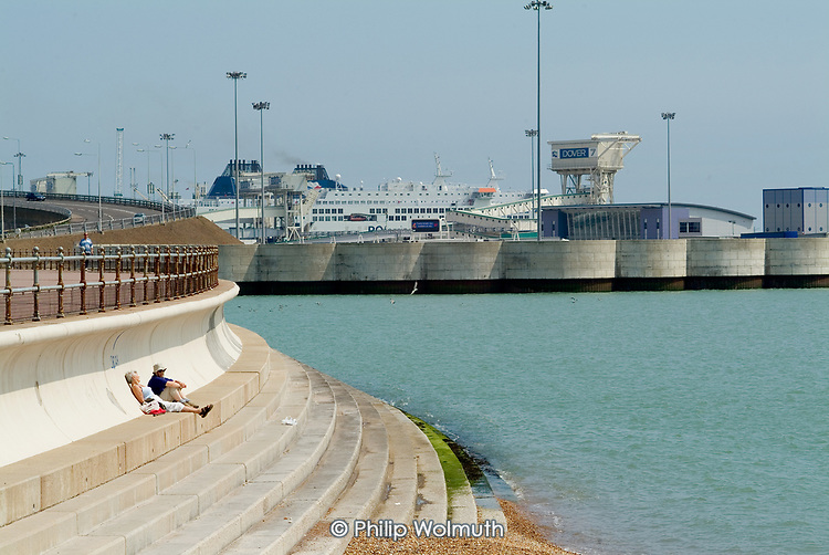 Two elderly sunbathers on the sea wall next to the Eastern Docks in Dover.