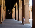 Cairo, Egypt -- Bright light shines through lovely arched openings into the arcades surrounding the central plaza and fountain at the historic ibn Tulun mosque.   © Rick Collier / RickCollier.com