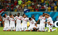Costa Rica players kneel at the half way line as they prepare to watch the final penalty in the shootout, with several players unable to watch the drama