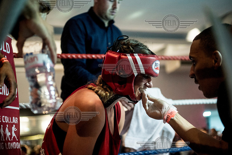 Emily Williams has her gum shield put in by a trainer at a white collar boxing event at the London Irish Centre where the 'Carpe Diem' boxing event is taking place. <br /> <br /> 'White-collar boxing' is a growing phenomenon amongst well paid office workers and professionals and has seen particular growth in financial centres like London, Hong Kong and Shanghai. It started at a blue-collar gym in Brooklyn in 1988 with a bout between an attorney and an academic and has since spread all over the world. The sport is not regulated by any professional body in the United Kingdom and is therefore potentially dangerous, as was proven by the death of a 32-year-old white-collar boxer at an event in Nottingham in June 2014. The London Irish Centre, amongst other venues, hosts a regular bout called 'Carpe Diem'. At most bouts participants fight to win. Once boxers have completed a few bouts they can participate in 'title fights' where they compete for a replica 'belt'.  <br /> <br /> <br /> <br /> <br /> <br /> <br /> ©Andrew Testa for the Sunday Times Magazine