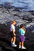 Two boys at lava flow of Kilauea volcano on the Big island of Hawaii