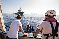"""Sea Watch-2.<br /> Die Sea Watch-2 bei ihrer 13. SAR-Mission vor der libyschen Kueste.<br /> Im Bild: Besprechung eines von Crewmitgliedern waehrend des Einsatzes. Im Hintergrund die """"Bourbon Argus"""" der Hiflfsorganisation """"Aerzte ohne Grenzen"""" (links) und ein spanisches Kriegsschiff der Frontex-Mission, welches zu keiner Zeit die Rettung der Menschen in Seenot unterstuetzt hat.<br /> 20.10.2016, Mediterranean Sea<br /> Copyright: Christian-Ditsch.de<br /> [Inhaltsveraendernde Manipulation des Fotos nur nach ausdruecklicher Genehmigung des Fotografen. Vereinbarungen ueber Abtretung von Persoenlichkeitsrechten/Model Release der abgebildeten Person/Personen liegen nicht vor. NO MODEL RELEASE! Nur fuer Redaktionelle Zwecke. Don't publish without copyright Christian-Ditsch.de, Veroeffentlichung nur mit Fotografennennung, sowie gegen Honorar, MwSt. und Beleg. Konto: I N G - D i B a, IBAN DE58500105175400192269, BIC INGDDEFFXXX, Kontakt: post@christian-ditsch.de<br /> Bei der Bearbeitung der Dateiinformationen darf die Urheberkennzeichnung in den EXIF- und  IPTC-Daten nicht entfernt werden, diese sind in digitalen Medien nach §95c UrhG rechtlich geschuetzt. Der Urhebervermerk wird gemaess §13 UrhG verlangt.]"""