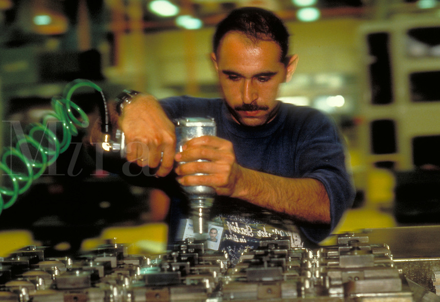 A factory worker working on machinery with a power tool. People. Professions. Factory worker. Israel.