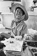 April 1970, Vientiane, Laos. An 8-year-old girl sells marijuana leaves and cigarettes in an open air market in Vientiane. Child labor as seen around the world between 1979 and 1980 - Photographer Jean Pierre Laffont, touched by the suffering of child workers, chronicled their plight in 12 countries over the course of one year.  Laffont was awarded the World Press Award and Madeline Ross Award among many others for his work.