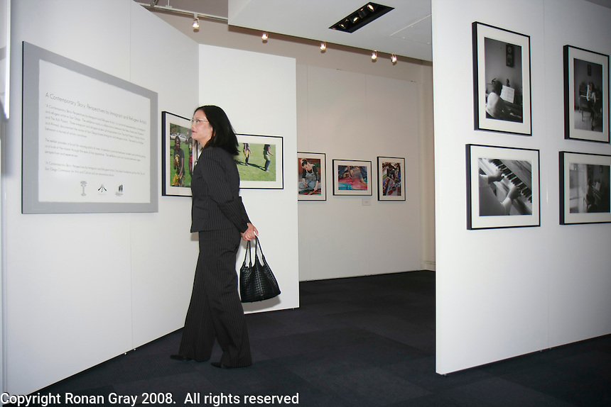 A visitor views the photographic exhibition in The New American Museum at the NTC Promenade in Liberty Station Friday, June 20, 2008.   The museum will feature exhibits, lectures and conferences related to immigration issues.  It will also house a recording studio where families can document their own immigrant history.