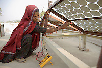 Kamla, age 33, is Rajasthan's first female solar engineer. Starting her education at age 11 in night school, while carrying on with her domestic and farm work, she went on to study solar technology and now runs a rural field station fabricating solar home lighting systems and solar lanterns. Despite her humble background she has travelled to Delhi to speak at National Conferences on solar technology. Here Kamla checks the voltage on rooftop solar panels and cleans the panels at a Barefoot College field station...