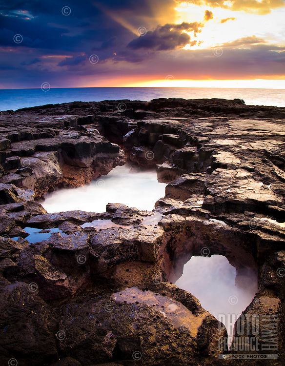 At sunset, waves surge through openings along Keahole Point's rocky shoreline on the Big Island.