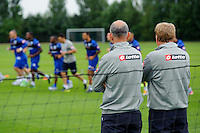 QPR manager Harry Redknapp watches his team train with assistant and Joe Jordan