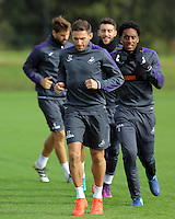 Pictured: Angel Rangel leads team mates as they warm up Thursday 29 September 2016<br /> Re: Swansea City FC training at Fairwood, Wales, UK