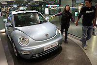 A young couple looks at a Volkswagon's Beetle in Beijing dealership, China..