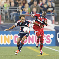 New England Revolution defender Kevin Alston (30) works to clear ball as Chicago Fire midfielder Patrick Nyarko (14) pressures. In a Major League Soccer (MLS) match, the New England Revolution (blue) defeated Chicago Fire (red), 1-0, at Gillette Stadium on October 20, 2012.