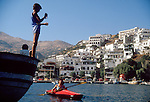 Crete, Sea kayaker in Crete: Ayia Galini, a young fisherman eyes Sarah as she paddles from the harbor of this SW coastal town. Circa 1990, Sarah Shannon, released,.