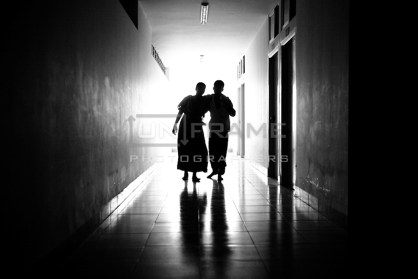 Shokhina with her husband Motin at Anam Medical College Hospital corridor. She worked in 6th floor at Rana Plaza and her both leg is seriously injured. Savar, Bangladesh.