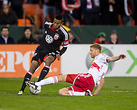 Lionard Pajoy (26) of D.C. United tries to cross the ball under the leg of Markus Holdgersson (5) of New York Red Bulls during the game at RFK Stadium in Washington DC. D.C. United tied New York Red Bulls, 1-1.