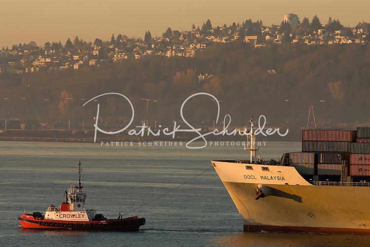 A tugboat boat pulls a cargo ship through Elliot Bay in Seattle Washington.