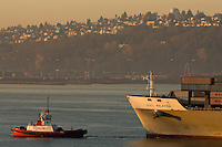 A tugboat boat pulls a cargo ship through Elliot Bay in Seattle Washington.