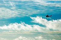 Seaplane flies across a cloudy sky, Maldives.