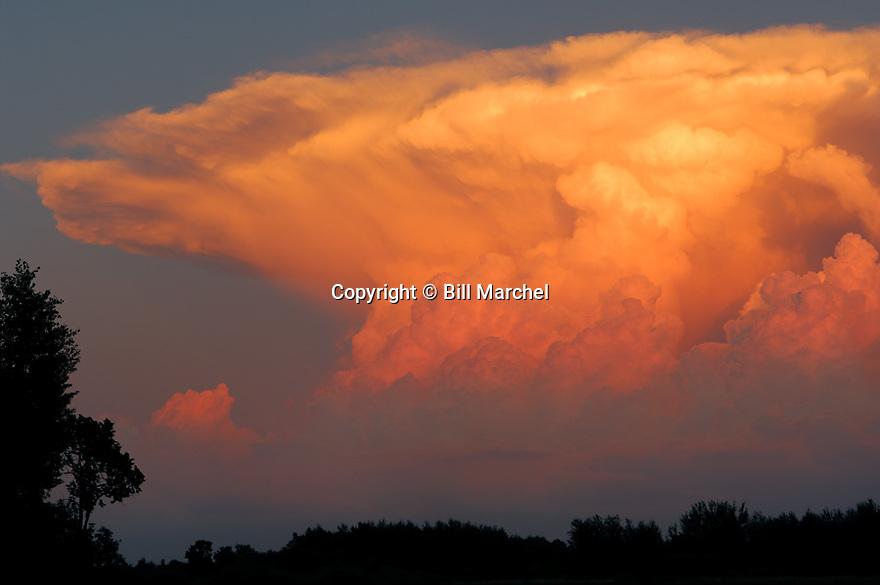 01180-002.18 Thunderstorm (DIGITAL) Anvil head thunderstorm cloud is lite by low sun.  Drama, weather, storm, rain, nature.  H0E1