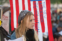 A protester in Zuccotti Park stands in front of an American flag with the words *The new American revolution* during the Occupy Wall Street demonstration in New York City, New York.
