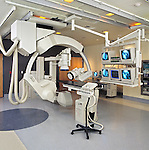 wide shot of empty catheritization operating room with heart x-ray visible on monitor array