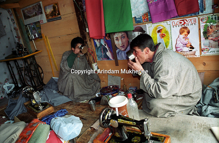 Two Kashmiri shop keepers having their lunch inside their shop having posters of Indian Hindi movie stars. They are fond of Hindi movies but the movie halls are closed due to militancy they watch such movies in Television. Before two decades Kashmir valley was a favourite shooting spot for Indian hindi film directors for its natural beauty. Srinagar, Kashmir valley, India