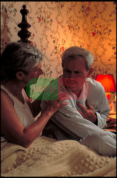 elder man in bed with chest pain while concerned woman comforts him