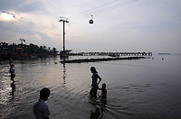 """A woman leads her child through the shallow waters off a beach in northern Jakarta. According to the Climate Reality Project, """"Without flood protection measures, sea level rise could expose up to 6 million Indonesians to annual coastal flooding. The worst of the flooding would occur on the island of Java, where Jakarta is located."""""""